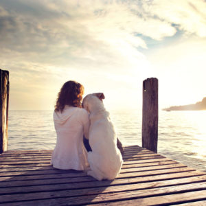 Woman sitting on dock with her dog