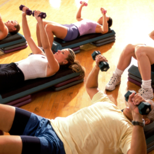 Five people exercising with weights and steps