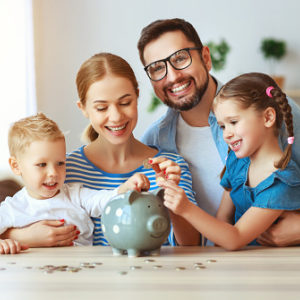 Mom and dad showing kids how to manage money with a piggybank
