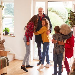 Children welcoming grandparents at the doorway during the holidays
