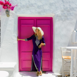 Woman on vacation smiling in front of pink door