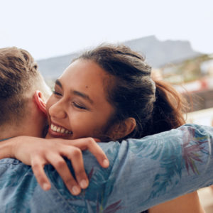 Woman greeting her male friend and embracing.