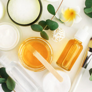Natural cosmetics ingredients for skincare, body and hair care. Golden honey in jar and green herbal eucalyptus leaves.
