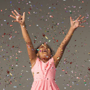 Young girl in party dress celebrating with confetti