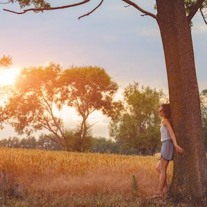 Girl leaning against an oak tree for strength and solace.
