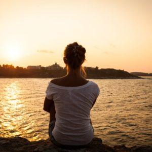 Woman facing water at sunset
