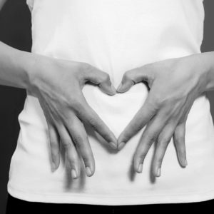 Woman's hands on stomach heart