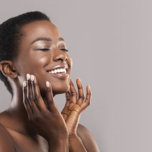 A woman massages her face as an embodiment practice