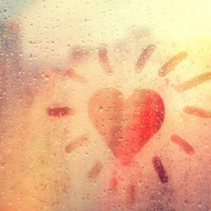 Hand-drawn orange, heart-shaped like sun on rainy window