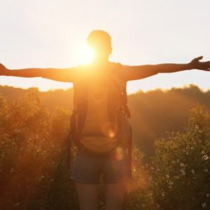 Woman hiker with arms outstretched to sun