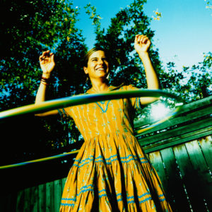 hula hooping in the sunlight under a tree