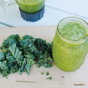 Green smoothie and kale on wood surface