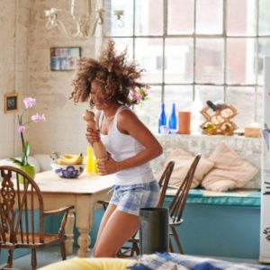 Curly-haired girl dancing in kitchen