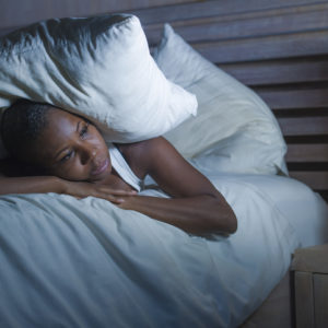 Woman with insomnia in bed with pillow over head