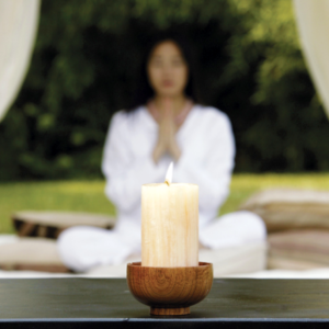 Woman meditating with candle
