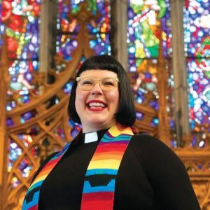 Rev Jes Kast with stained glass windows behind and a rainbow stole over shoulders