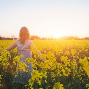 Woman with arms raised in field of flowers