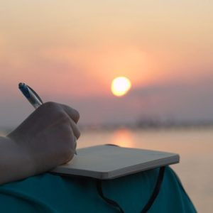 Woman journaling at sunset