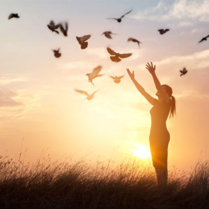 Woman releasing birds at sunset