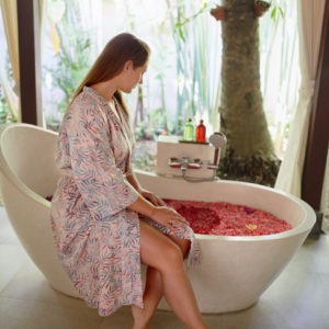 Woman in robe sitting on edge of bath covered in rose petals