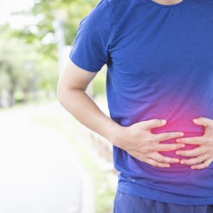 Man with an inflamed gut doubles over in pain, illustrating how CBD can help with stomach issues