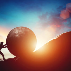 True Grit: Man pushing huge concrete ball up hill