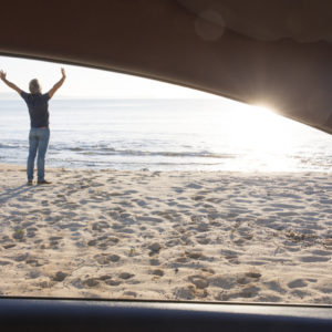 "<img src=""man-stretches-outside-car.jpg"" alt=""man on the beach stretches outside his car""/>"