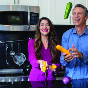 Mark Hyman and Mia Lux laughing and holding vegetables
