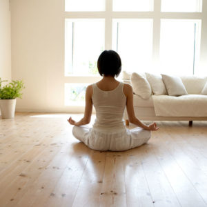 Woman meditating in light room