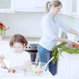 A girl and her mother cooking in kitchen