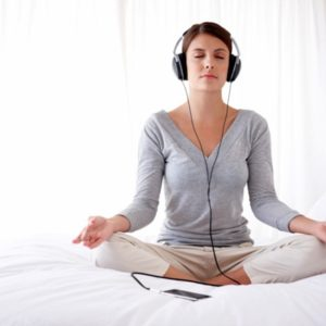 woman listening to music in lotus position