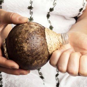 Woman pours coconut oil into hands