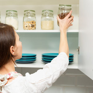 Woman reaching for jar in kitchen cabinet