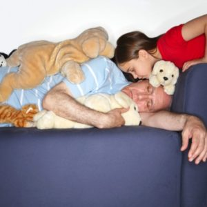 Parent covered with stuffed animals on couch