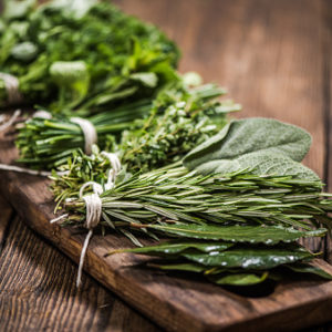 Bunches of parsley, sage, rosemary, and thyme on wooden plank