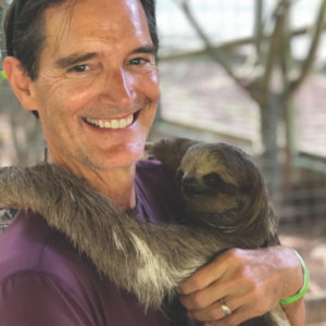 Paul Sutherland holding a sloth
