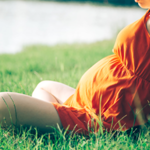 Pregnant woman sitting in grass