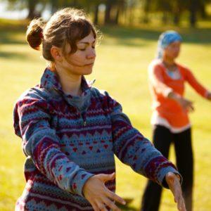 Two women practicing qigong in nature