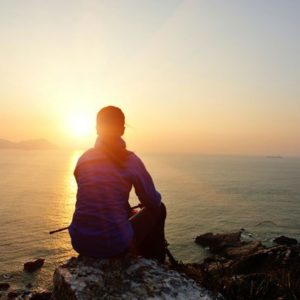 Woman sits on rock and watches sunset