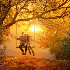 Couple swinging on swing in fall