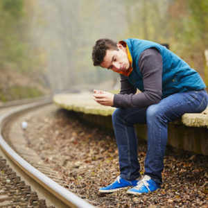 Boy sitting on train tracks