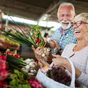 Senior couple holding vegetables and carrying basket in produce aisle of market