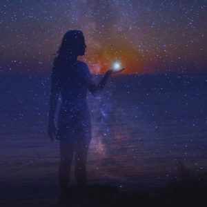 The night sky full of stars and a silhouette of a standing girl with a star in her hand