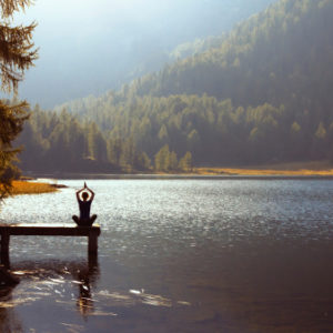 Woman practicing meditation and yoga at sunset on a pier on a forest lake