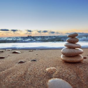 Balancing stones on beach at sunrise