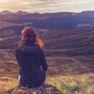 Woman gazing over rugged landscape