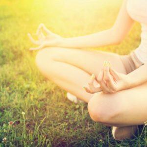 Woman meditating on grass