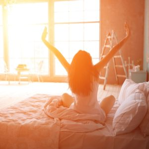 Woman stretching in bed with sunlight
