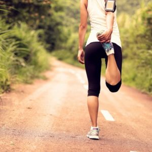Woman stretching leg on dirt road