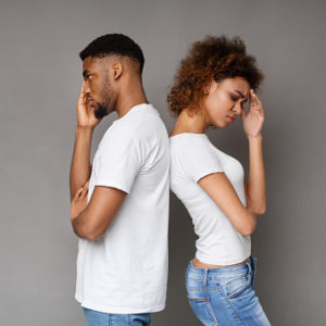 Upset couple standing back to back in front of gray background